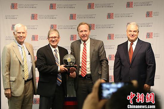图为该基金会主席尼尔·布什(右二)向代为领奖的卡特之子詹姆斯·厄尔·卡特(左二)颁发中美关系卓越领袖奖。 中新社记者 曾静宁 摄