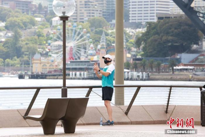 当地时间4月19日,悉尼风和日丽,民众走出家门,享受运动时光。根据相关规定,运动不在受限之列。图为悉尼歌剧院外一位戴口罩的运动青年停下脚步,用手机拍下美景。中新社记者 陶社兰 摄