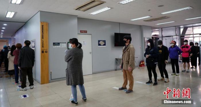 在韩国首尔一投票站,民众保持距离,排队等候投票。 中新社记者 曾鼐 摄