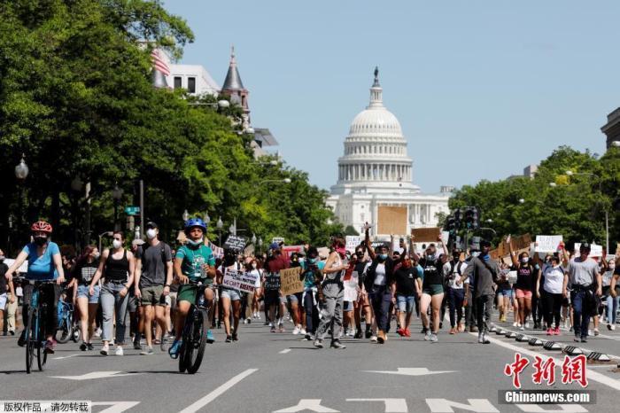 资料图:当地时间5月30日,美国华盛顿,抗议者高举标语从国会山朝白宫进发。