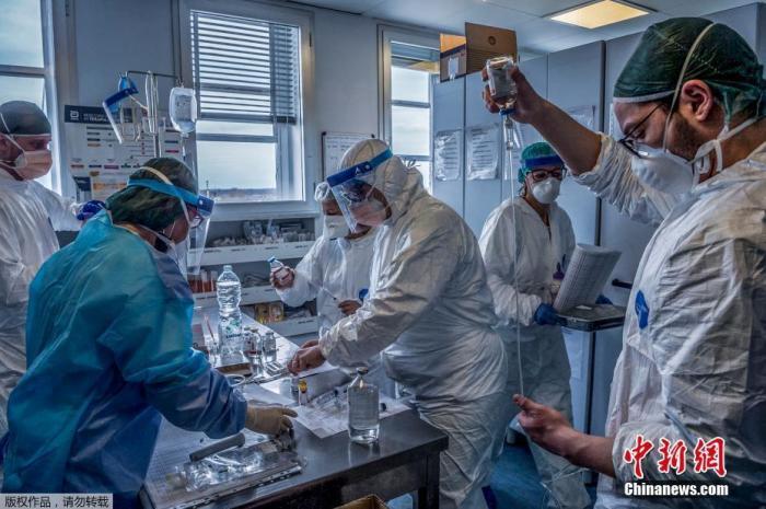 当地时间3月23日,探访意大利米兰东南部的克雷莫纳医院重症监护室,医护人员正在为感染新冠状肺炎的重症患者治疗。