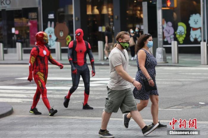 当地时间8月9日,美国纽约时代广场的行人和电影人物表演者。